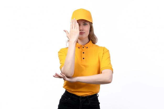 Uma vista frontal jovem correio feminino trabalhadora do serviço de entrega de comida sorrindo posando com a mão erguida em branco