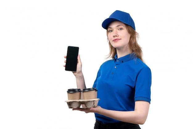 Uma vista frontal jovem correio feminino trabalhadora do serviço de entrega de comida sorrindo segurando copos e telefone de café em branco