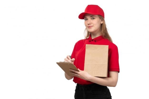 Uma vista frontal jovem correio feminino trabalhadora do serviço de entrega de comida sorrindo segurando o bloco de notas em branco