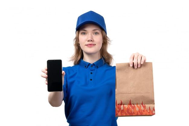 Uma vista frontal jovem correio feminino trabalhadora do serviço de entrega de comida sorrindo segurando pacote de alimentos e smartphone sorrindo em branco