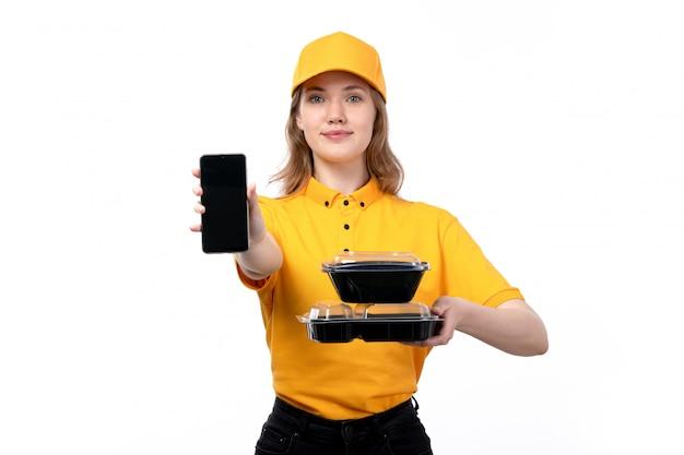 Uma vista frontal jovem correio feminino trabalhadora do serviço de entrega de comida sorrindo segurando smartphone e tigelas com comida em branco