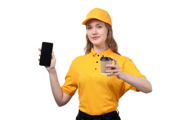 Uma vista frontal jovem correio feminino trabalhadora do serviço de entrega de comida sorrindo segurando smartphone e xícara de café em branco