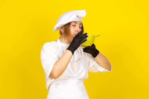 Uma vista frontal jovem cozinheira feminina em traje de cozinheiro branco e boné branco em luvas pretas, segurando a placa verde comendo espaguete no amarelo