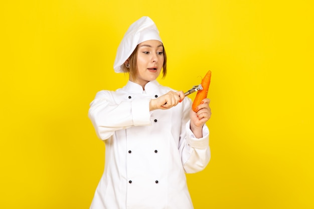 Uma vista frontal jovem cozinheira feminina no fato de cozinheiro branco e tampa branca segurando e limpando carrott laranja no amarelo