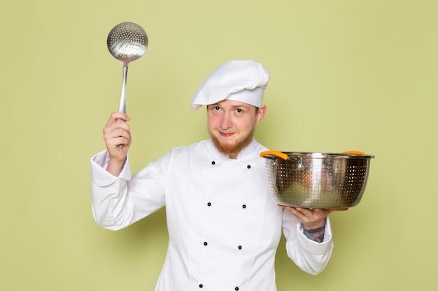 Uma vista frontal jovem cozinheiro masculino em branco cozinheiro terno branco cabeça cap segurando a panela de prata e metálica com colher de prata grande