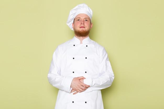 Uma vista frontal jovem cozinheiro masculino em branco cozinheiro terno branco cabeça tampa permanente
