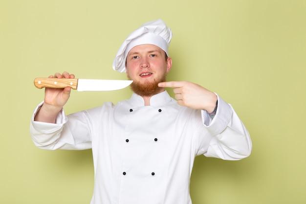 Uma vista frontal jovem cozinheiro masculino em branco cozinheiro terno branco cabeça tampa segurando a faca