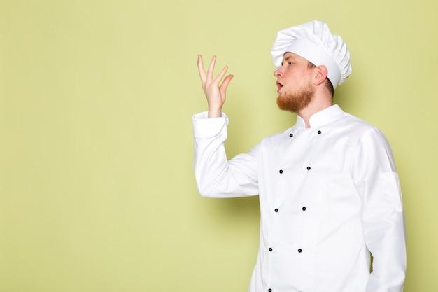 Uma vista frontal jovem cozinheiro masculino em branco cozinheiro terno branco cabeça
