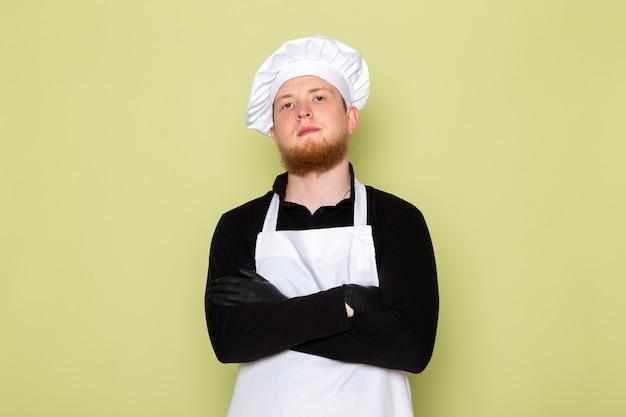 Uma vista frontal jovem cozinheiro masculino na camisa preta com capa branca cabeça branca em luvas pretas posando