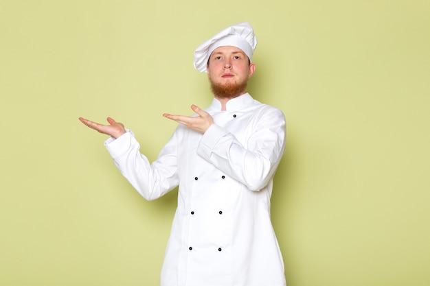 Uma vista frontal jovem cozinheiro masculino no cozinheiro branco terno boné de cabeça branca com as mãos levantadas