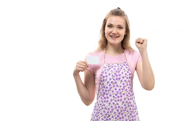 Uma vista frontal jovem dona de casa bonita na camisa rosa capa colorida feliz segurando cartão branco sorrindo