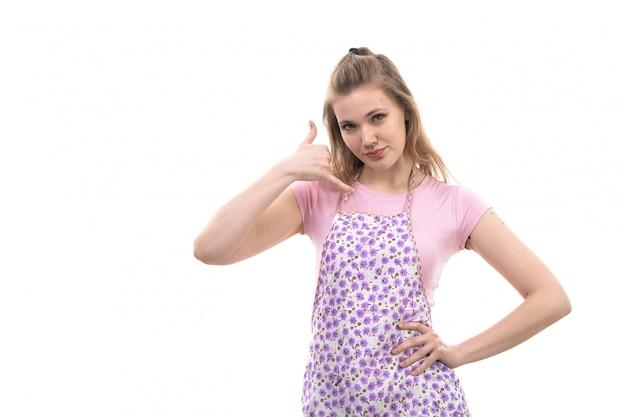 Uma vista frontal jovem dona de casa bonita na capa colorida de camisa rosa mostrando sinal de conversa de telefone