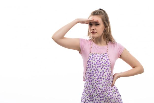 Uma vista frontal jovem dona de casa bonita na capa colorida de camisa rosa, olhando para a distância