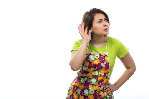 Uma vista frontal jovem dona de casa bonita na capa colorida de camisa verde tentando ouvir