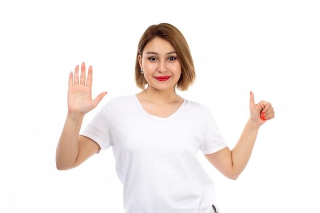 Uma vista frontal jovem em t-shirt branca posando sorrindo mostrando como sinal no branco