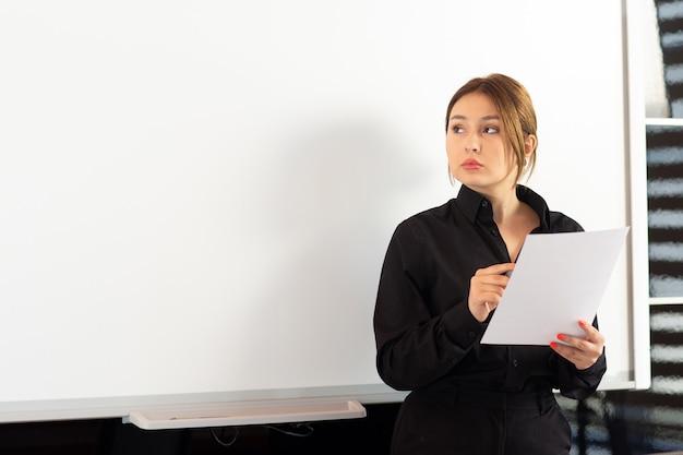 Uma vista frontal jovem empresária atraente na camisa preta, apresentando seu trabalho lendo o documento