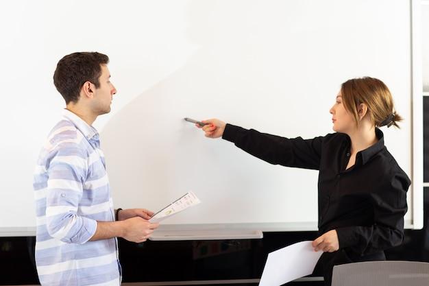Uma vista frontal jovem empresária atraente na camisa preta junto com o jovem discutindo gráficos sobre a mesa enquanto a jovem apresenta seu trabalho lendo o documento de apresentação de documentos
