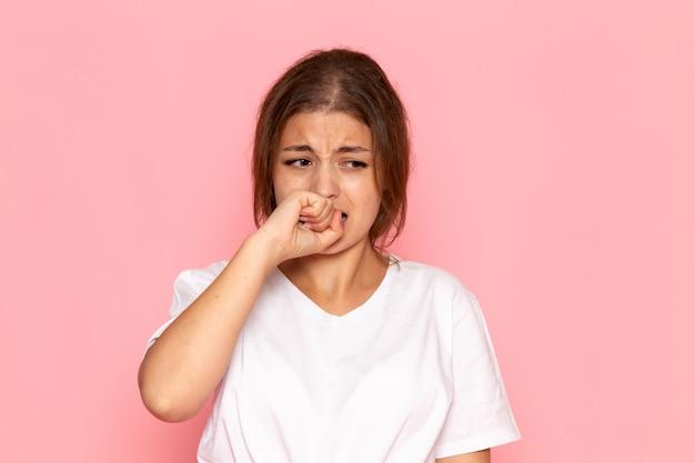 Uma vista frontal jovem fêmea bonita na camisa branca com expressão triste e assustada