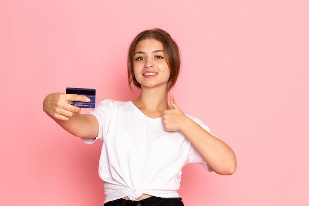 Uma vista frontal jovem fêmea bonita na camisa branca com segurando o cartão roxo