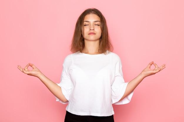 Uma vista frontal jovem fêmea bonita na camisa branca em pose de meditação