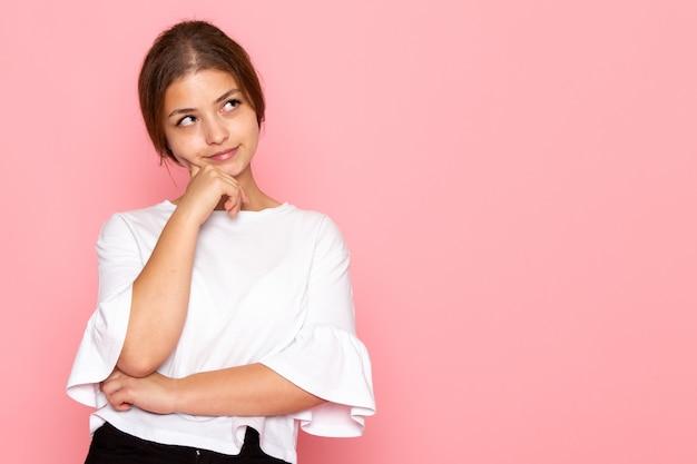Uma vista frontal jovem fêmea bonita na camisa branca posando com expressão a sonhar