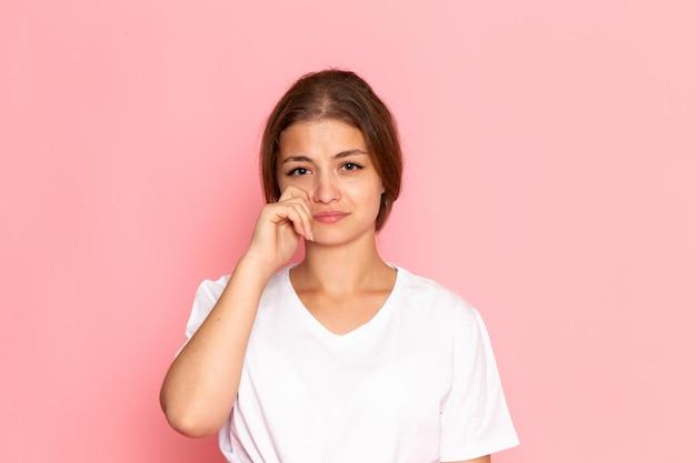 Uma vista frontal jovem fêmea bonita na camisa branca posando com lágrimas nos olhos