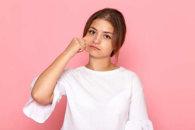 Uma vista frontal jovem fêmea bonita na camisa branca, tirando a bochecha
