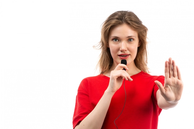 Uma vista frontal jovem fêmea de camisa vermelha, falando através de microfone em branco