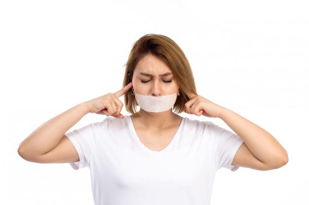 Uma vista frontal jovem fêmea de camiseta branca e calça jeans preta com bandagem branca em volta da boca, fechando os ouvidos no branco