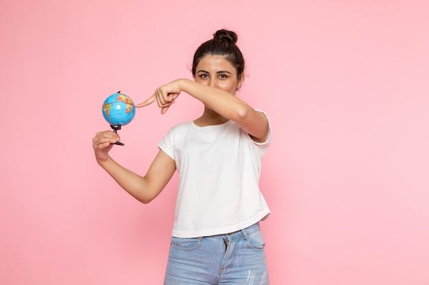 Uma vista frontal jovem fêmea em t-shirt branca e azul jeans posando com sorriso segurando o globo pequeno
