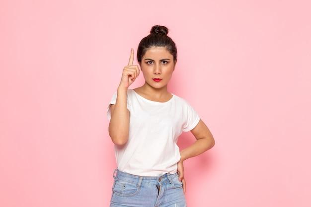 Uma vista frontal jovem fêmea em t-shirt branca e azul jeans posando