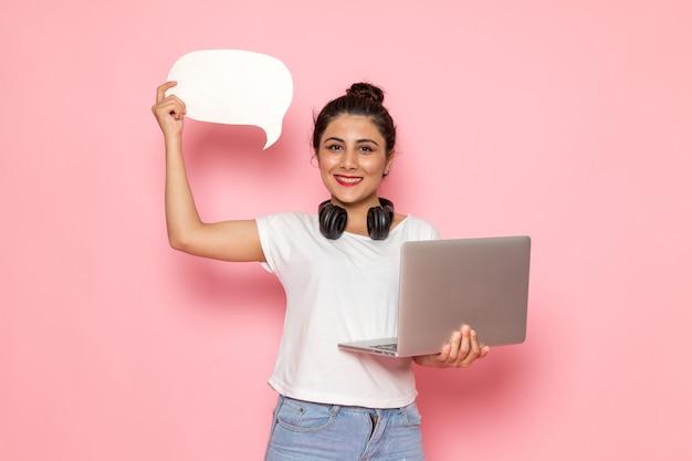 Uma vista frontal jovem fêmea em t-shirt branca e azul jeans segurando laptop e placa branca