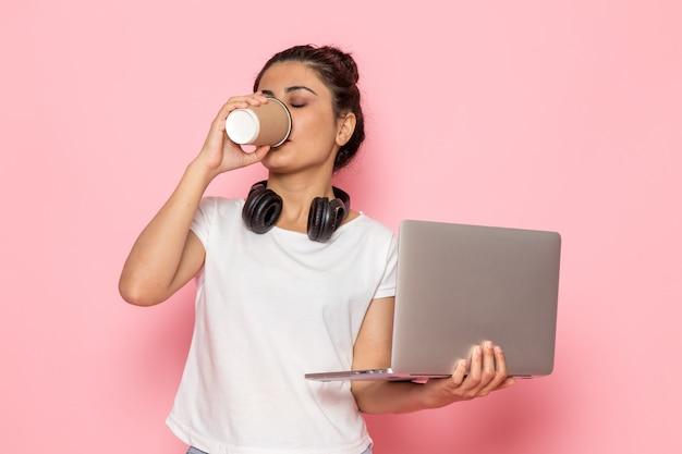 Uma vista frontal jovem fêmea em t-shirt branca e azul jeans usando laptop e bebendo café
