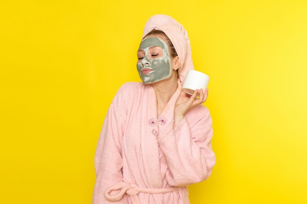 Uma vista frontal jovem fêmea linda em roupão rosa segurando creme para o rosto