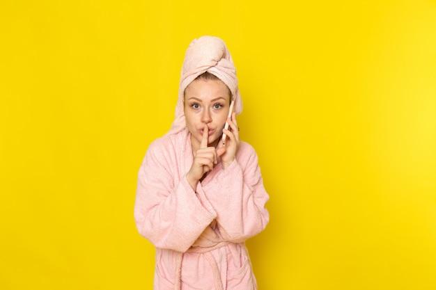 Uma vista frontal jovem fêmea linda em roupão rosa talkign no telefone em silêncio