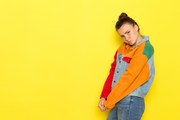 Uma vista frontal jovem fêmea na camisa amarela colorida jaqueta e calça jeans triste