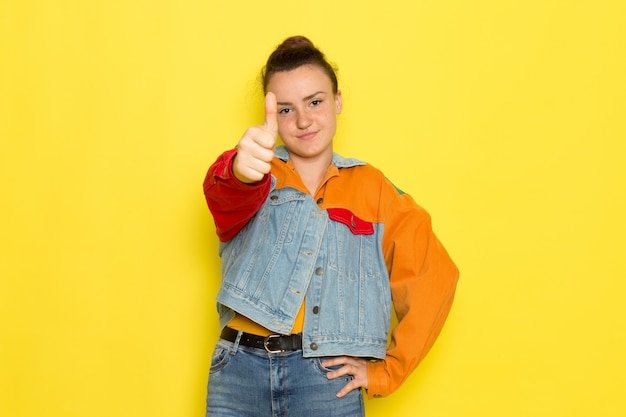 Uma vista frontal jovem fêmea na camisa amarela jaqueta colorida e azul jeans posando