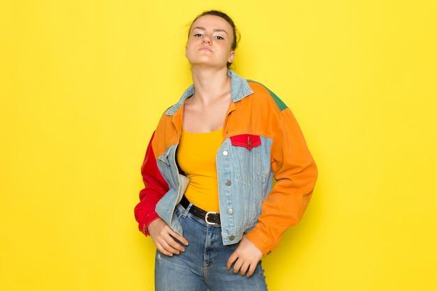 Uma vista frontal jovem fêmea na camisa amarela jaqueta colorida e jeans azul apenas boxe