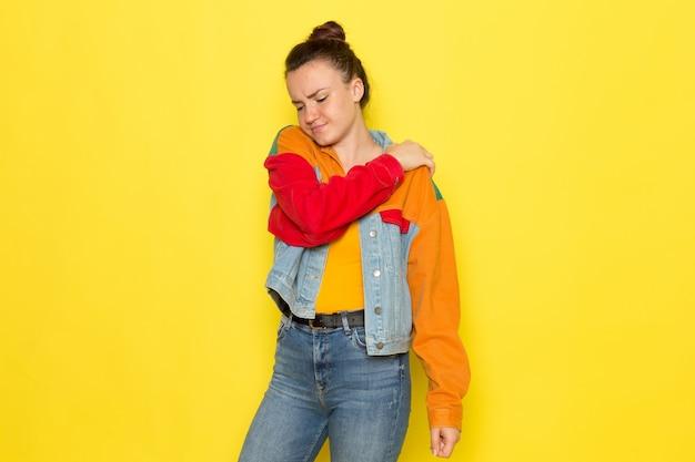 Uma vista frontal jovem fêmea na camisa amarela jaqueta colorida e jeans azul, tendo uma dor nas costas