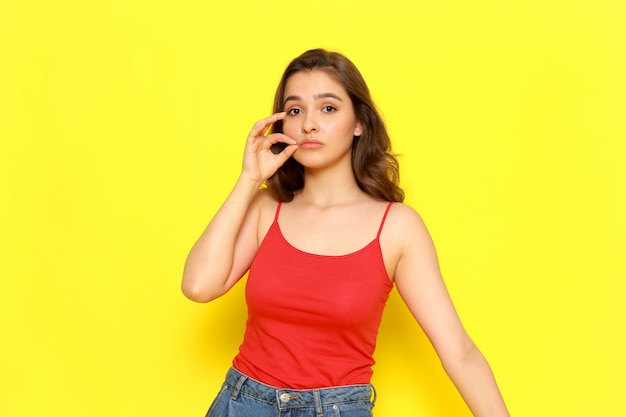 Uma vista frontal jovem garota bonita camisa vermelha e calça jeans azul, fechando a boca