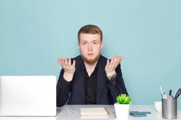Uma vista frontal jovem homem atraente com barba em emoções de terno moderno clássico preto escuro com as mãos levantadas no espaço azul