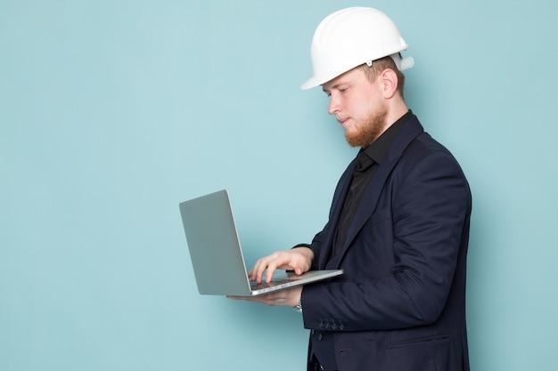 Uma vista frontal jovem homem atraente com barba no capacete de construção preto escuro clássico moderno terno branco usando laptop cinza no espaço azul