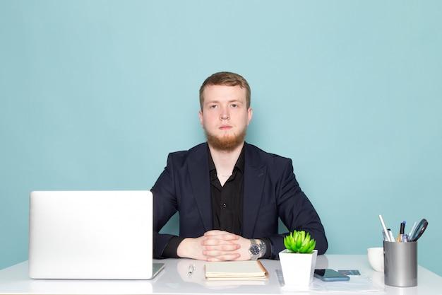 Uma vista frontal jovem homem atraente com barba no terno moderno clássico escuro preto no espaço azul