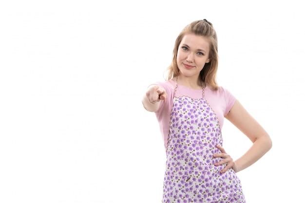 Uma vista frontal jovem linda dona de casa na capa colorida camisa rosa sorrindo apontando