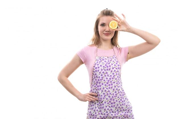 Uma vista frontal jovem linda dona de casa na capa rosa camisa colorida feliz sorrindo segurando laranja meio corte cobrindo o olho