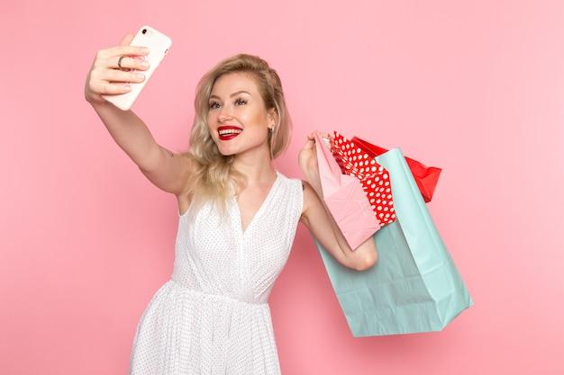 Uma vista frontal jovem linda no vestido branco segurando pacotes de compras com sorriso no rosto, tendo um selfie moda roupas femininas
