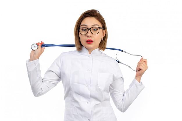 Uma vista frontal jovem médica em traje médico branco com estetoscópio no branco