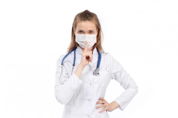 Uma vista frontal jovem médica em traje médico branco com estetoscópio usando máscara protetora branca posando sinal de silêncio no branco