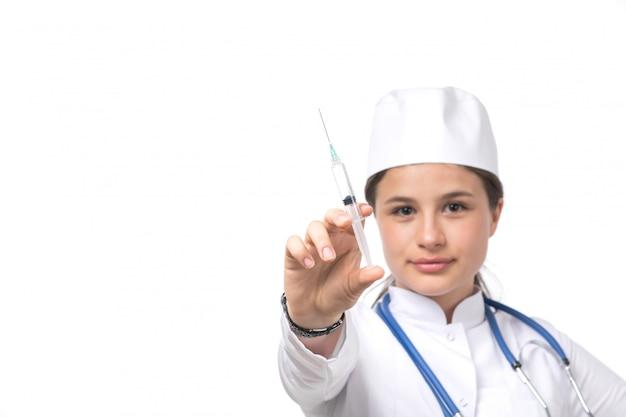 Uma vista frontal jovem médica em traje médico branco e boné branco com estetoscópio azul segurando a injeção
