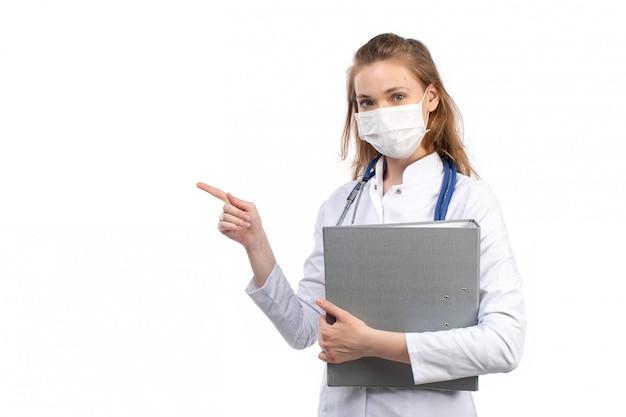 Uma vista frontal jovem médica no terno médico branco com estetoscópio usando máscara protetora branca segurando arquivos cinza no branco